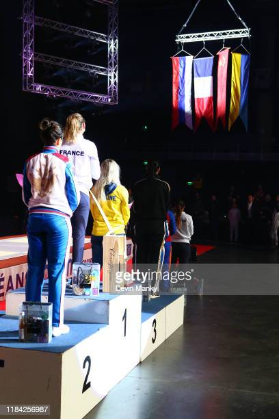 Manon Brunet of France stands atop the podium in Orleans while Olga Nikitina is in 2nd and Olga Khlaran and Yaqi Shao are in third and and watches...