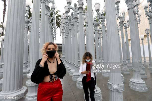Manon Guijarro left, who just graduated from Pierce College, puts on her mask after her friend Paige Johnson finished taking her personal graduation...