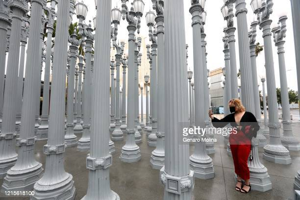 Manon Guijarro takes a picture of her friend Paige Johnson off camera, at Chris Burdens outdoor, Urban Light, at the Los Angeles County Museum of Art...