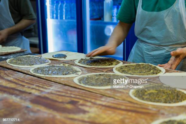 manouche, lebanese flatbread, with zaatar prepared in bakery, beirut, lebanon - libanon stock-fotos und bilder