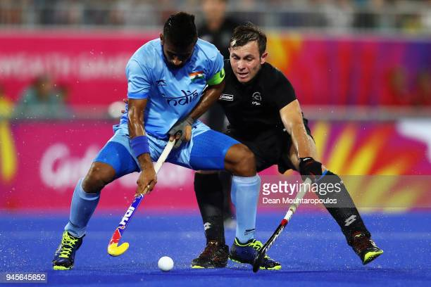 Manpreet Singh of India battles for the ball with Hayden Phillips of New Zealand during Men's Semifinal match between India and New Zealand on day...