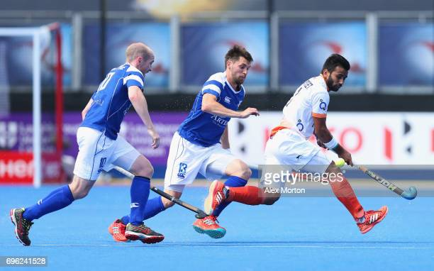 Manpreet Singh of India is watched by Gordan McIntyre and Kenny Bain of Scotland during the Pool B match between India and Scotland on day one of...