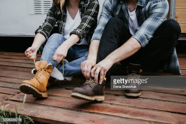 man's and woman legs in blue jeans and brown boots on wooden floor - ブーツ ストックフォトと画像