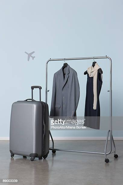Man's and woman's outfits hanging on clothes rack near suitcase, plane symbol in background