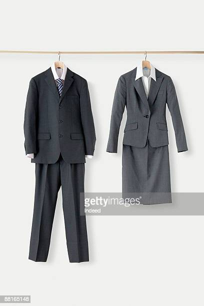 Man's and woman's suit hanging on bar