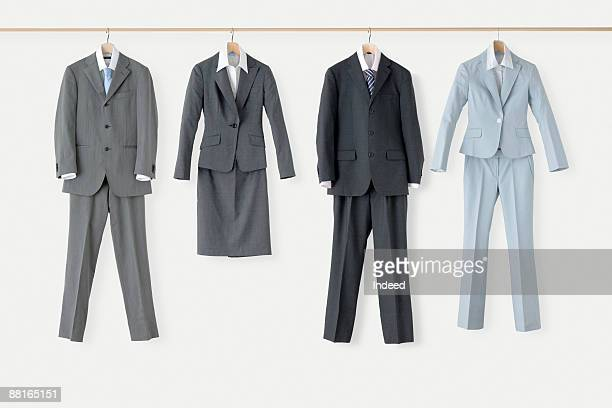 man's and woman's suits hanging on bar - zakelijke kleding stockfoto's en -beelden