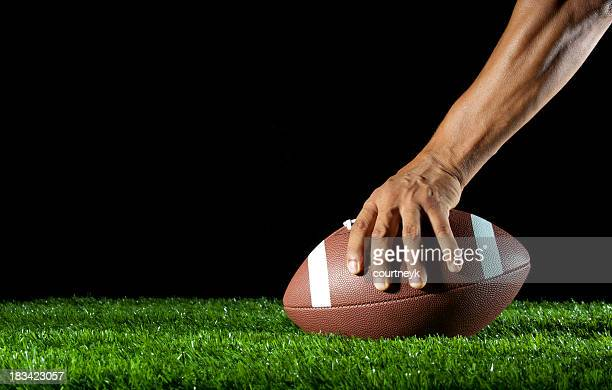 Mans arm hiking a football