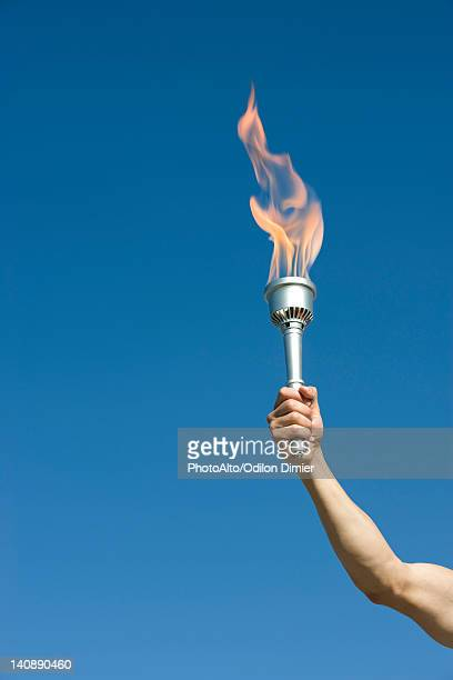 man's arm holding up torch - the olympic games stock pictures, royalty-free photos & images