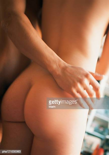 man's arm on nude woman's hip, mid-section, rear view - bare bottom stock pictures, royalty-free photos & images