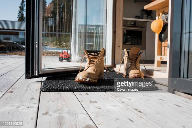 mans boots on a mat at the back door on a balcony at home - human doormat foto e immagini stock