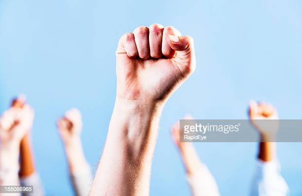 Man's clenched fist raised in triumph or defiance, against blue