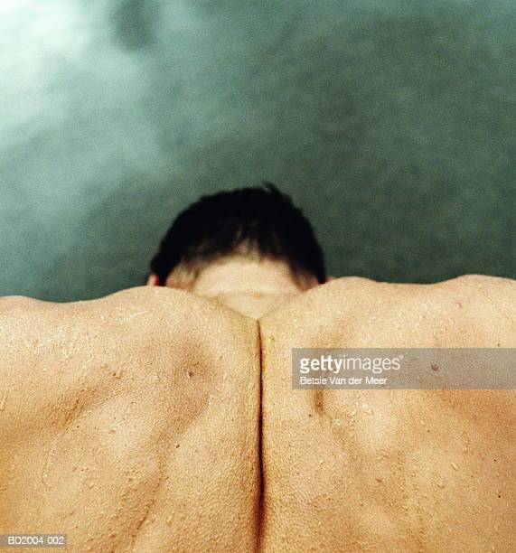 Man's clenched shoulders, close-up, elevated view