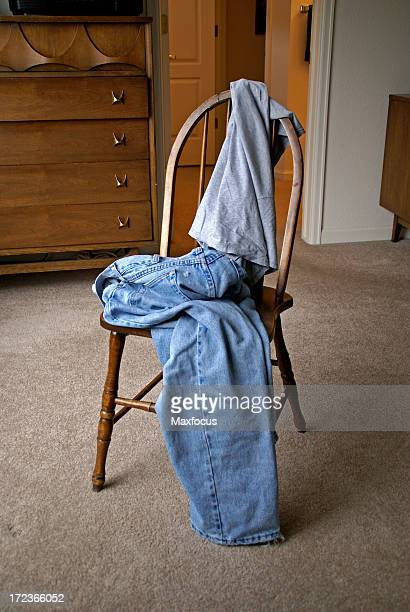 A mans clothes draped over a wooden chair