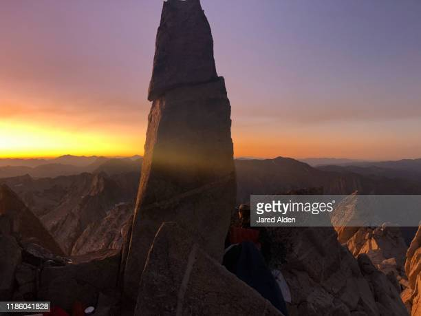 man's face illuminated in the light of watching a sunset on top of the matterhorn peak overlooking the sawtooth ridge mountains on the border of inyo national forest and yosemite national park - pinnacle peak stock pictures, royalty-free photos & images