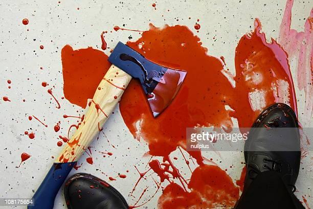 Mann's Füße und Axt in Pfütze von Blut