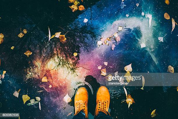 Man's feet and reflection of night sky and space in a puddle of water
