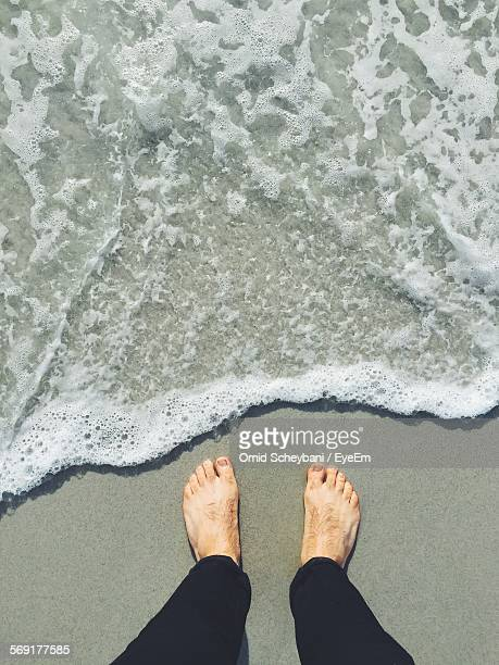 Mans feet by waters edge