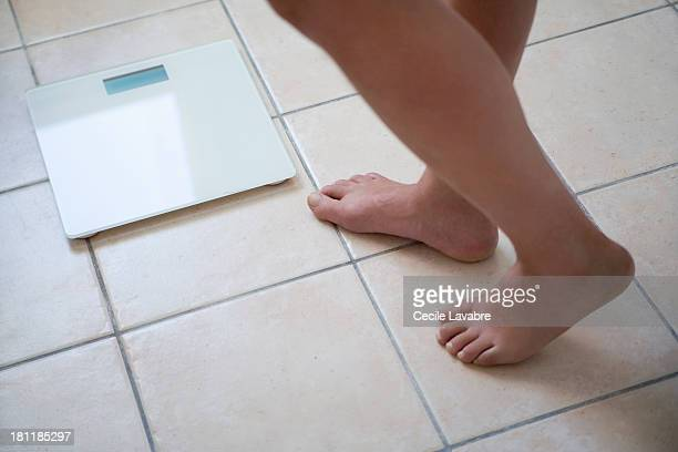 Man's feet going on a weighing scale