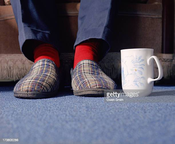 Mans feet in slippers with mug of tea
