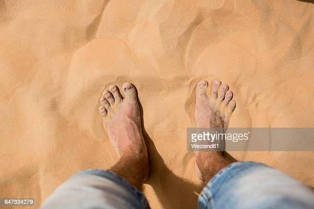 UAE, mans feet in the desert sand
