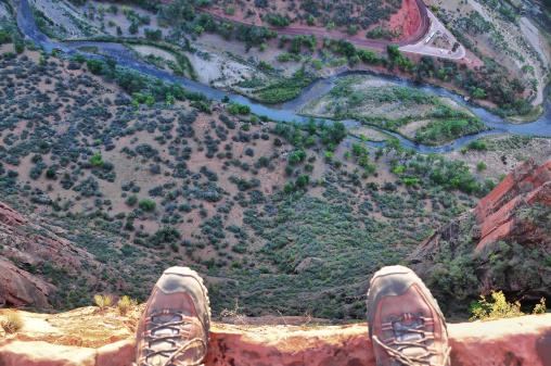 Man's feet on the edge of rock cliff 469881727