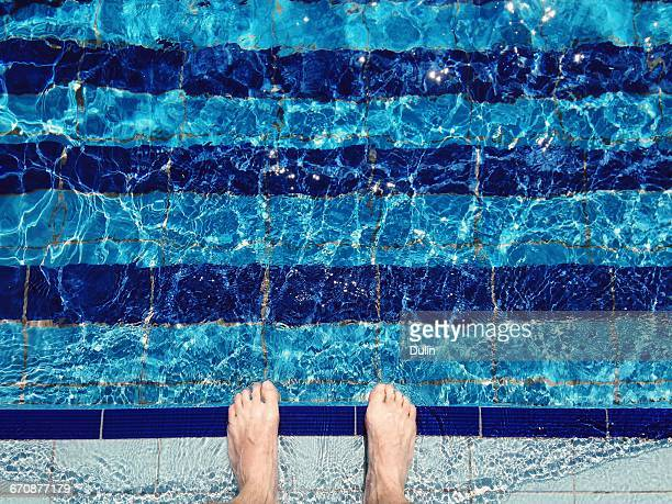 man's feet standing at the edge of swimming pool - taking the plunge stock photos and pictures