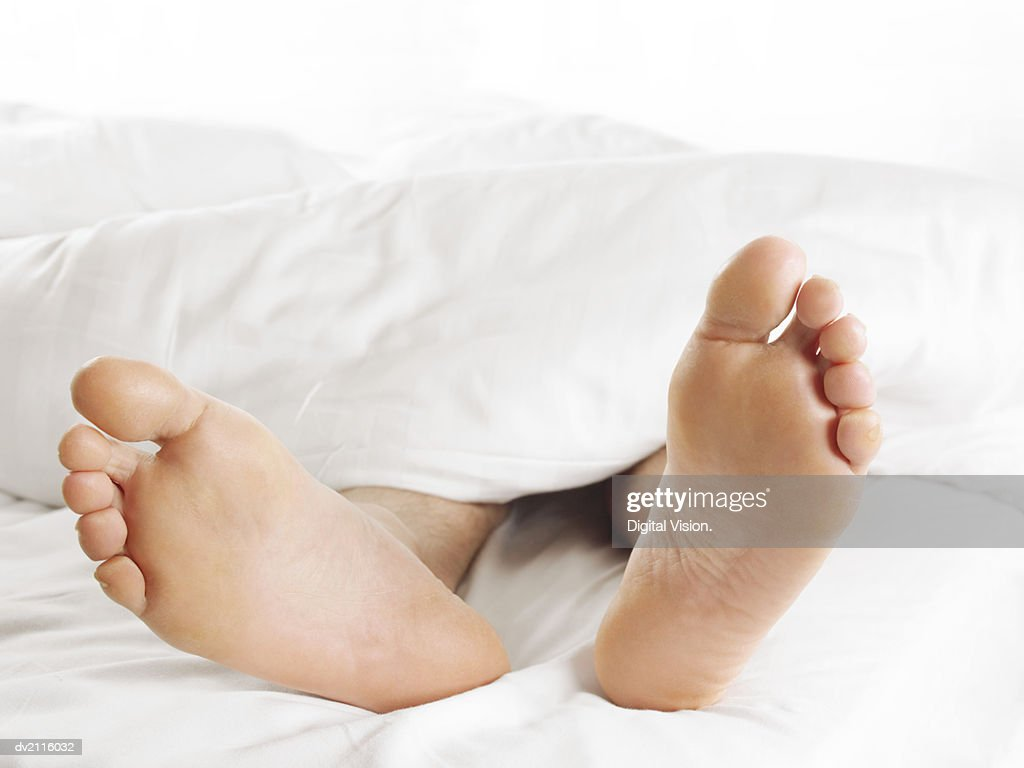 Man's Feet Underneath a Duvet in Bed : Stock Photo