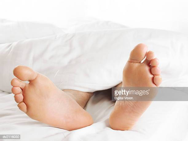 man's feet underneath a duvet in bed - male feet soles stock photos and pictures