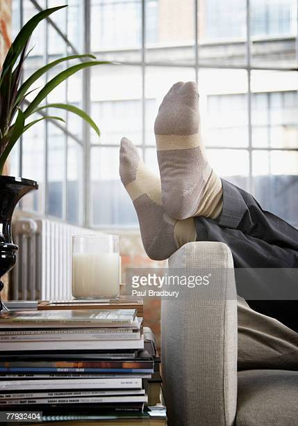 man's feet up on arm of couch in modern home - feet up stock pictures, royalty-free photos & images