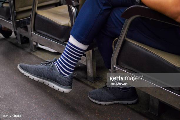 man's feet with striped socks on a train - blue shoe stock pictures, royalty-free photos & images