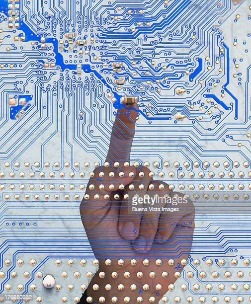 man's finger pointing a circuit board