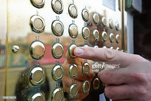 Man's finger pressing button on brass plaque