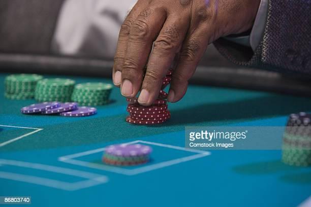 Man's fingers stacking poker chips