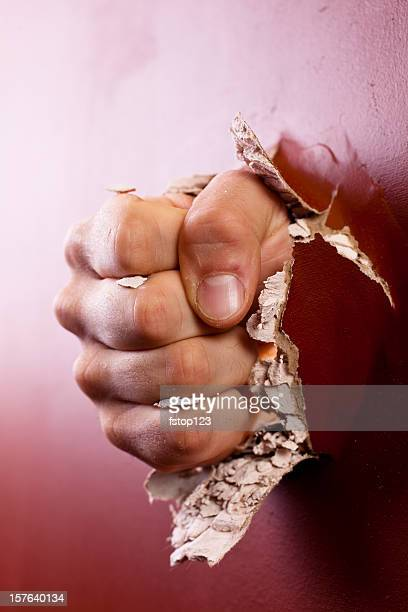 Man's fist coming through wall.