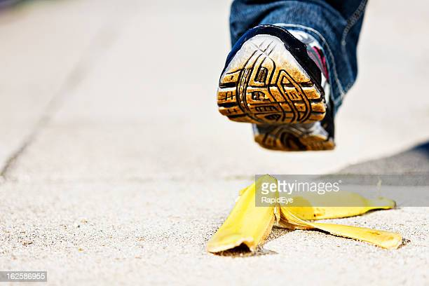 Man's foot approaches slippery banana peel on pavement: accident coming!
