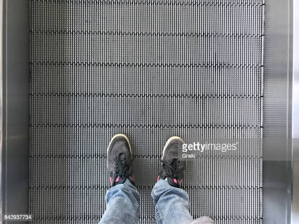 Man's foot in airport escalator perspective view