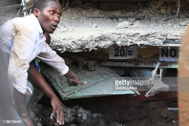 TOPSHOT A man's foot sticks out from under the rubble while he is trapped under the rubble after a sixstorey building collapsed in Nairobi on...