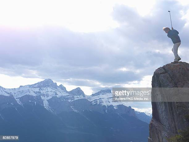 mans golfs off high cliff, above mountains - out of context stock pictures, royalty-free photos & images