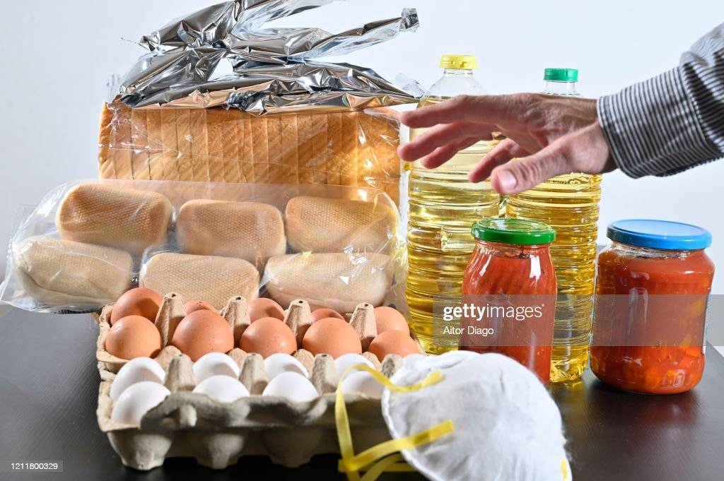 Man's hand approaching food on the table and a protective mask from viruses, allergies etc. Basic food on a table storable for a long time. Eggs, oil, bread, tomato cans and bags of potato puere : Stock Photo