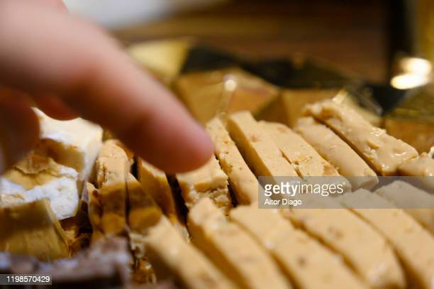 man's hand catching a piece of nougat. typical christmas food in spain. - nougat stock pictures, royalty-free photos & images