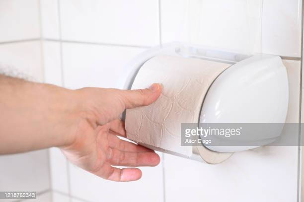man's hand changing toilet paper in a wc. - hemorroida imagens e fotografias de stock