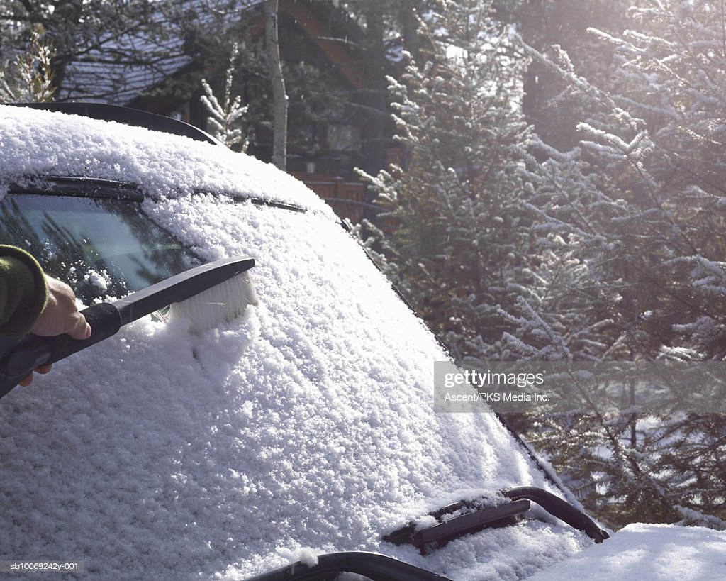 Man's hand clearing snow from car windscreen : Stockfoto
