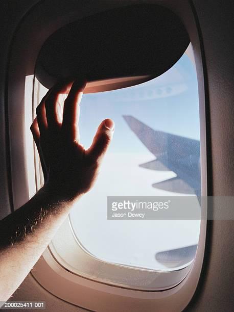 Man's hand closing airplane window