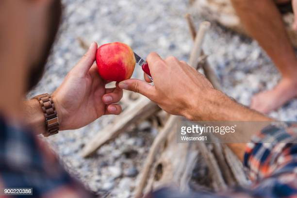 Mans hand cutting apple at camp fire