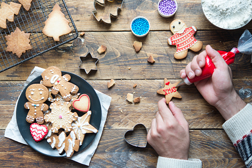 Man's hand decorating Christmas cookie - gettyimageskorea