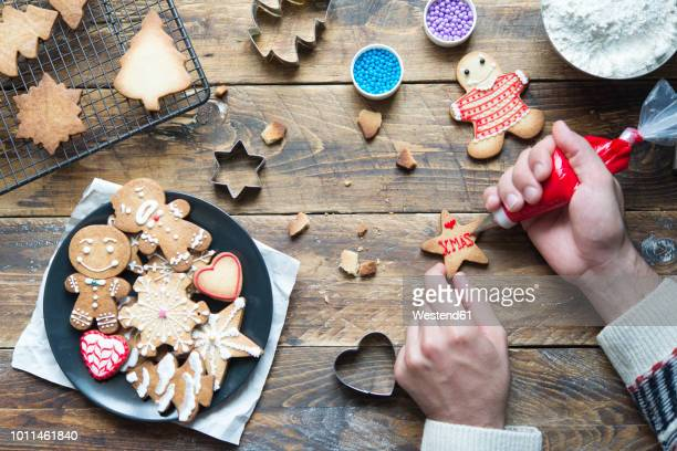 man's hand decorating christmas cookie - christmas cookies stock pictures, royalty-free photos & images