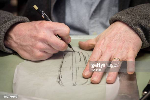 A man's hand drawing a sketch on transparent paper