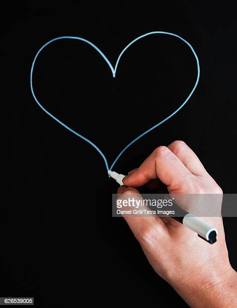 Mans hand drawing heart shape on black paper
