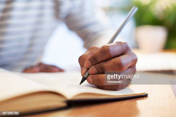 man's hand drawing in a notebook - writing activity stock photos and pictures