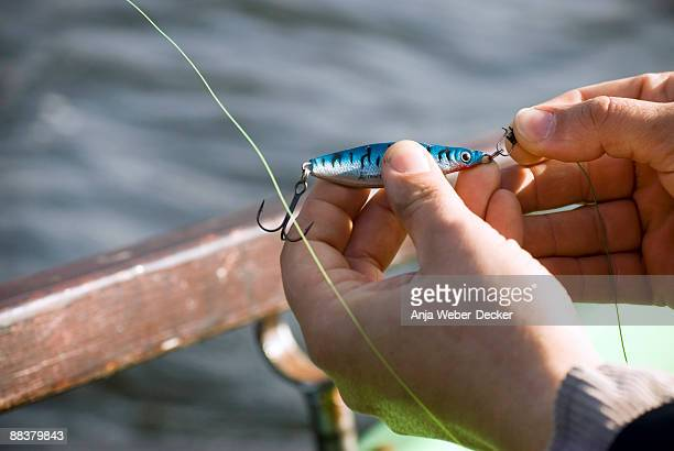 Man's hand fixing bait on hook, elevated view, close-up